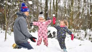 Children and a man play in the snow