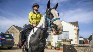 Rescue pony Micky helps owner Abi Eliot-Williams deliver library books to members of the Hullavington Book Group in the village of Hullavington near Malmesbury, Wiltshire.