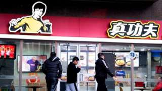 People walk past the restaurant Real Kung Fu, or Zhen Gongfu in Mandarin, run by fast food chain Kungfu Catering Management, in Beijing.