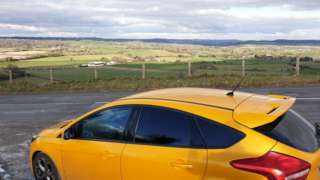 Yellow car parked in layby overlooking countryside