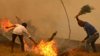 Residents of Baglung district in western Nepal battle forest fires