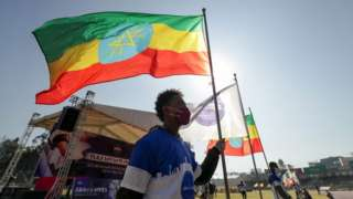 A volunteer holds an Ethiopian flag during a blood donation ceremony for the injured members of Ethiopia's National Defense Forces (ENDF) fighting against Tigray's special forces on the border between Amhara and Tigray, at the stadium in Addis Ababa, Ethiopia November 12, 2020.