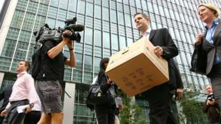 A Lehman Brothers employee carrying his work possessions in a cardboard box