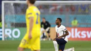 Photograph showing Raheem Sterling taking the knee before a match.