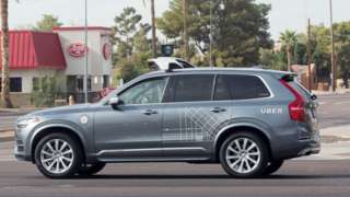 A mettalic grey Volvo car, wrapped with some occasional Uber branding in white vinyl, is seen here with a large mount on top of the vehicle which houses self-driving equipment