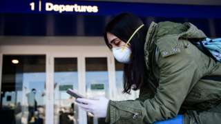 A passenger wearing a protective face mask looks her phone in Linate Airport in Milan