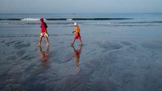 Locals walking across Ashvem Beach, Mandrem, Goa, India during sunset on November 28, 2014.