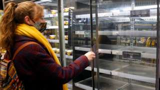 A customer wearing a protective face mask looks at empty shelves inside a Marks & Spencer food store on 6 January 2021 in Paris, France