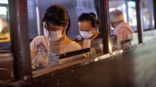 Pessoas de máscara de cabeça baixa no ônibus