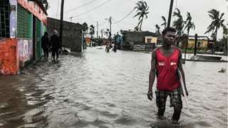A man walks down a flooded road