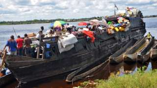 A barge on the Congo river filled with passengers and cargo