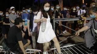 woman walks over barrier to prevent Tiananmen vigil in HK