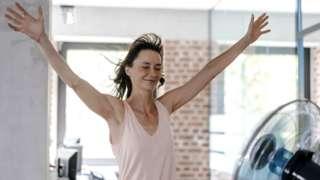 Businesswoman in office enjoying breeze from a fan - stock photo