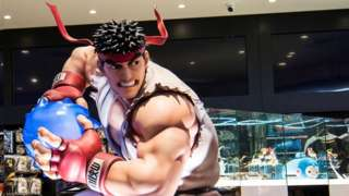 """A life-size statue of Ryu from Street Fighter, in his iconic white karate suit and red bandana, prepares a """"hadouken"""" energy ball. In the background is a Capcom brand store"""