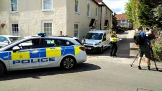 The body of the woman, in her 50s, was discovered at a house in Vicarage Lane, Hambledon