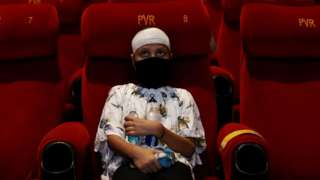 A person watching a movie in Delhi after cinemas reopen