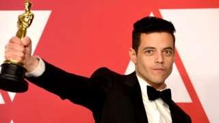 Rami Malek holding up his Oscar