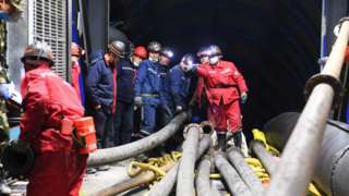 Rescuers work at the site where a coal mine flooded in Hutubi county