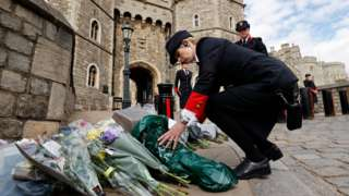 Wardens of the Castle move floral tributes to the side of the driveway at the Henry VIII Gate of Windsor Castle