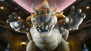 A statue of Bowser is seen with arms raised in a scaring pose in the Nintendo theme park