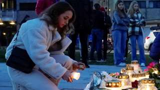 A woman lights a candle in Kongsberg, Norway,