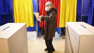 A woman votes at a polling station in Bucharest during parliamentary elections on 6 December 2020