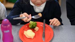 A pupil eats her cooked hot dinner