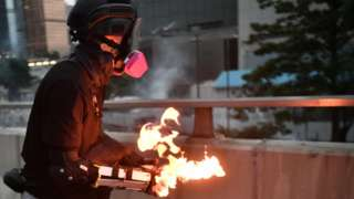 A protester prepares to throw a molotov cocktail towards police in the Admiralty area