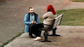 man proposing to woman on bench