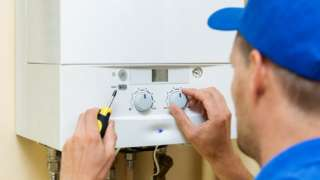 Worker sets up central gas heating boiler at home