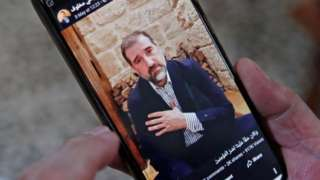 Picture of Rami Makhlouf on a mobile phone