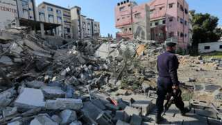 Hamas policeman walks past the remains of a building in Gaza City destroyed in an Israeli air strike (26 March 2019)