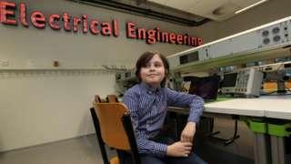 Simons aparece sentado em cadeira dentro de laboratório, sorrindo
