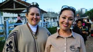 Friends Claudia Matiello and Raquel Oliveira pose for a photo