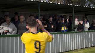 A Marske United player applauds the fans
