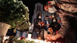 People lights candle outside the Notre-Dame de l'Assomption Basilica in Nice on October 29, 2020