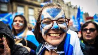 Young woman with Scotland flag painted on her face