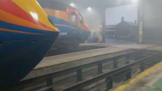 Train pulling into a foggy depot