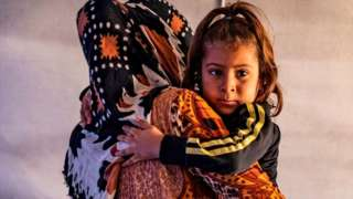 Displaced woman and child in Tuwaynah, north-east Syria (file photo)