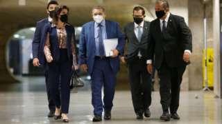 Kassio Nunes caminha de máscara em corredor, com outras pessoas atrás