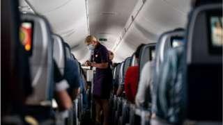 Aeromoça de máscara em avião