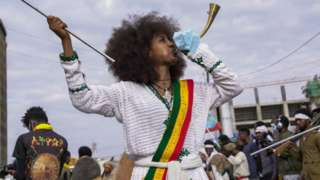 A woman blows a trumpet ahead a procession to mark the victory at the Battle of Adwa - March 2021, Addis Ababa, Ethiopia