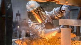 A metal worker wearing face protection