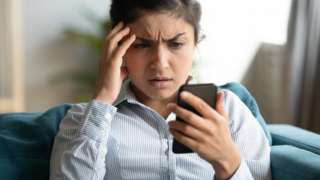 A woman looking anxiously at her phone