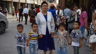 A Uighur woman waiting with children on a street in Kashgar in China's northwest Xinjiang region.