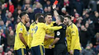 Referee raises a red card to Arsenal players