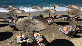 Tourists enjoy the sun on the beach at Ermones in Corfu, Greece