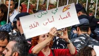 متظاهرة لبنانية ترفع لافتة منددة بالفساد