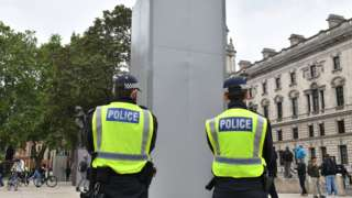 Police officers stand beside the now encased Churchill statue on Parliament Square