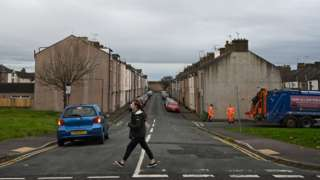Refuse collectors work on a street in Workington, north west England on November 6, 2019